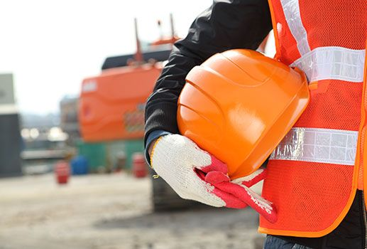 A worker holding a hardhat during a temporary site shutdown