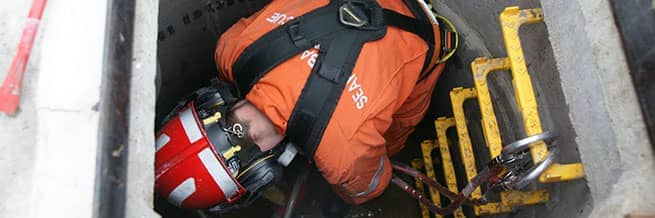A worker entering a confined space