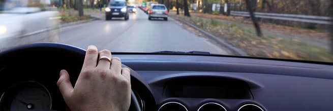 A driver with their hand on the wheel using proper defensive driving skills to stay safe on the road.