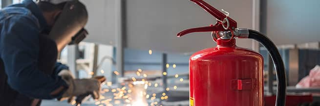 A welder in the distance with spark flying and a fire extinguisher in the foreground for fire watch