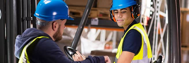 A forklift training instructor speaking with an operator