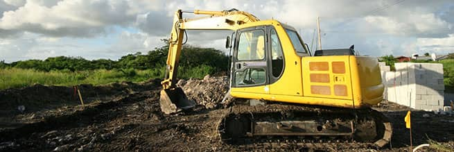 An excavator breaking ground on a construction site following proper ground disturbance protocol.