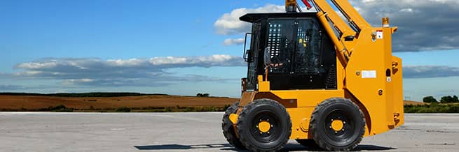 A yellow skid steer with the bucket raised