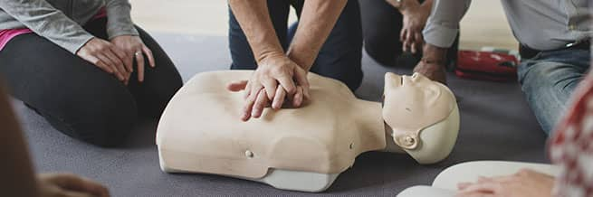 An instructor in standard first aid demonstrating proper CPR procedures