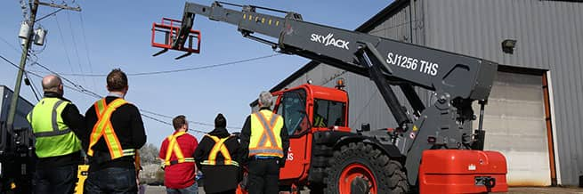 A telehandler training course in progress with people in PPE looking at a telehandler